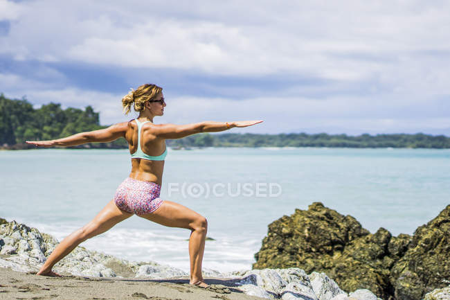 Beautiful woman doing yoga on beach with arms outstretched in Costa rica, Central America — Stock Photo