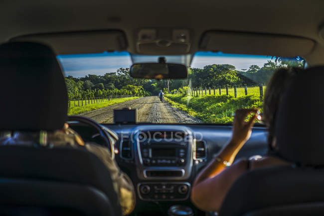 Road view from cars backseat with rear view of passengers on seats — Stock Photo