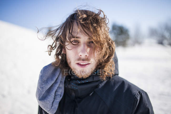 Young man standing in snow with long hair during cold winterday — Stock Photo