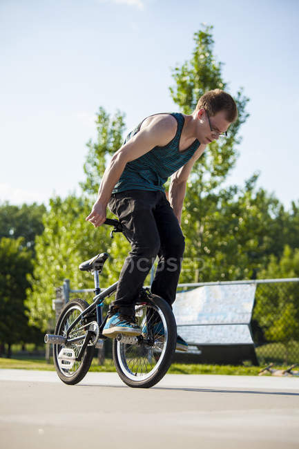Young teenager on bmx bike in skate park performing tricks — Stock Photo