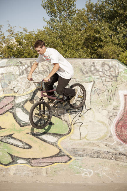 Young teenager riding bmx bike in skate park performing tricks — Stock Photo
