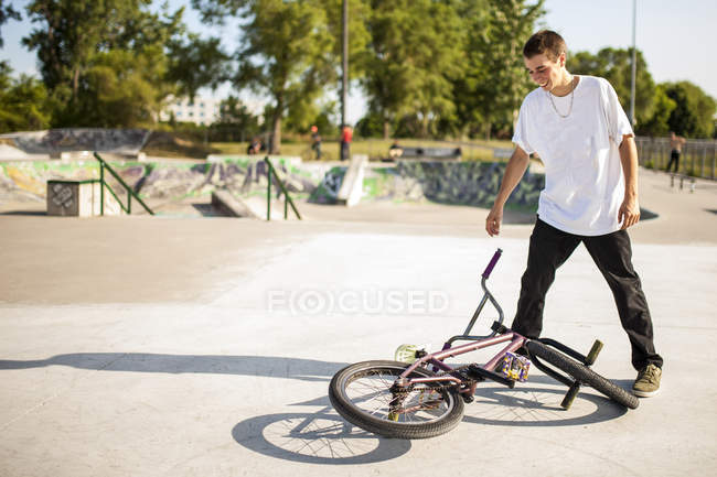 Teenager standing over bmx bike in skate park during summer — Stock Photo