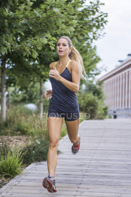 Blonde female working out and running on urban boardwalk — Stock Photo