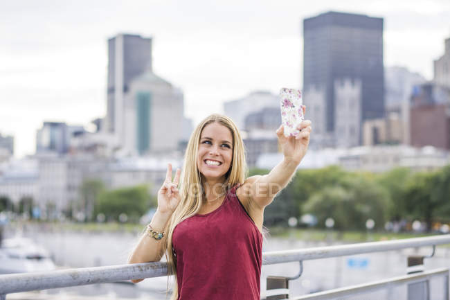 Stylish blonde girl in urban setting using smart phone and making selfie with peace sign — Stock Photo