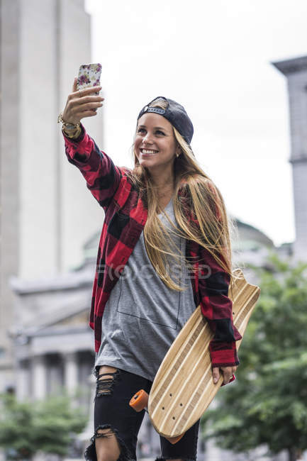 Stylish blonde girl with skate taking selfie in urban scene — Stock Photo