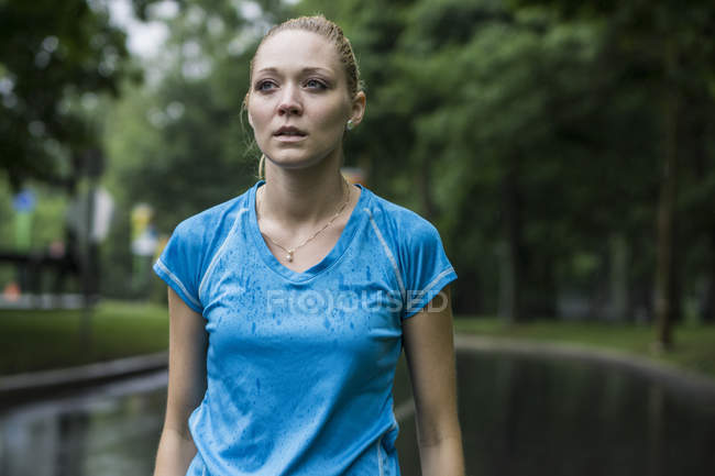 Young woman in wet t-shirt standing outdoors — Stock Photo