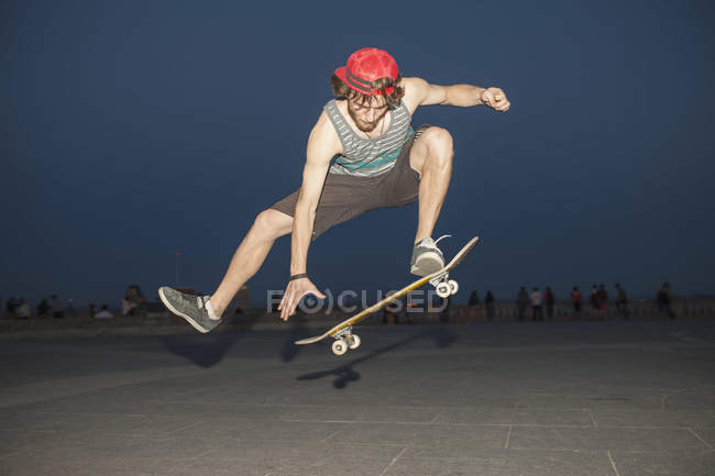 Young skateboard enthusiast flpping his board at night — Stock Photo