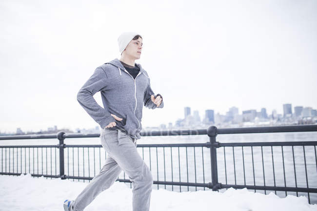 Young man in jogging pants running against fence — Stock Photo