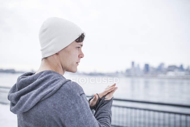 Young man in hat warming up hands along water — Stock Photo