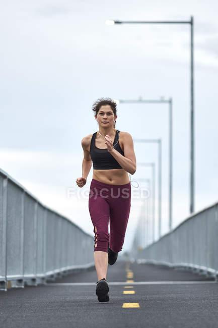 Confident woman running while training on bridge — Stock Photo