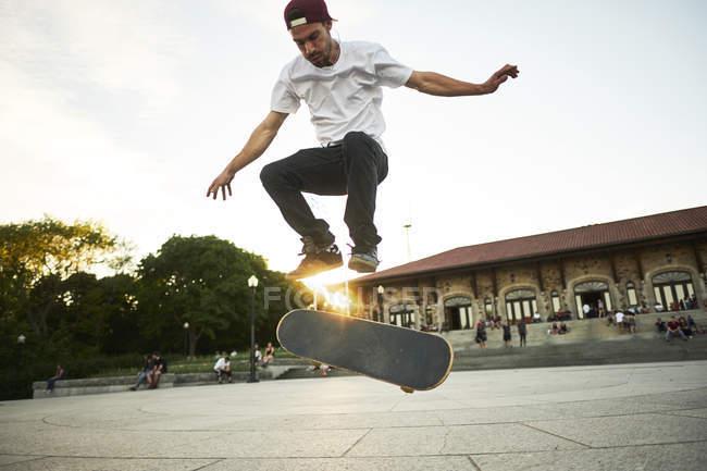 Passionné de skateboard, faire un truc flip tout en planche à roulettes dans le parc — Photo de stock
