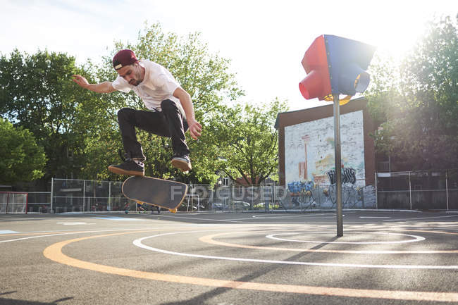 Man doing kickflip while skateboarding in park — Stock Photo