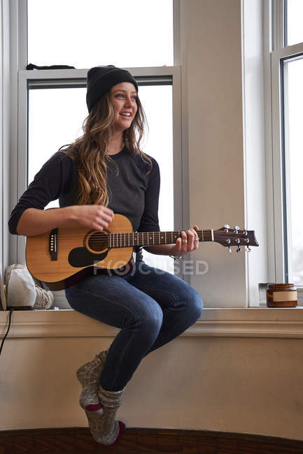 Young female musician playing guitar in the morning — Stock Photo