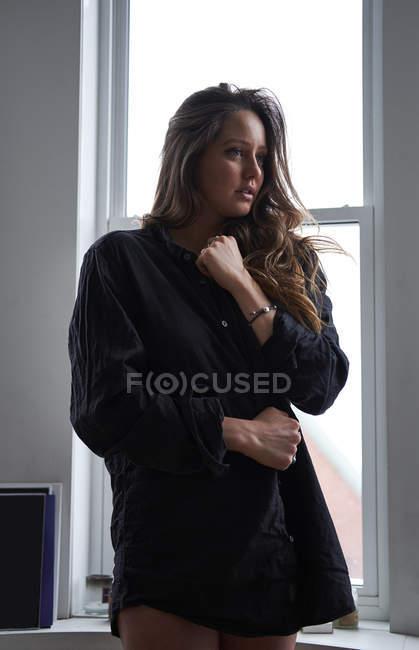 Женщина в черной рубашке рано утром внутри ее квартиры — стоковое фото