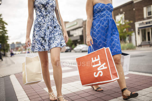 Cropped view of two women with shopping bags in small town — Stock Photo