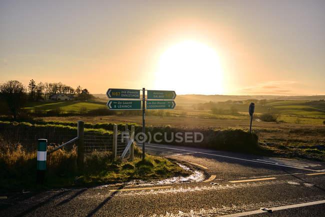 Intersection de la route avec directions signe près de Doolin au coucher du soleil, comté de Clare, en Irlande, Europe — Photo de stock