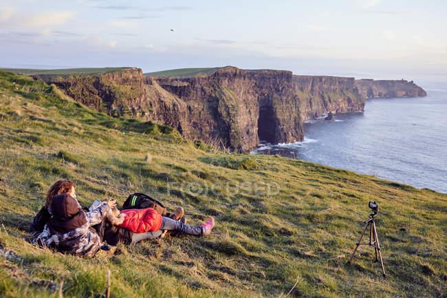 Скалы Мохер с семьей наблюдения пейзаж на закате, графство Клэр, Ирландия, Europe — стоковое фото