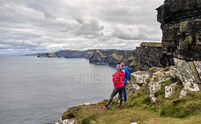Путешественники, изучение скалы Мохер на пасмурную погоду, графство Клэр, Ирландия, Европа — стоковое фото