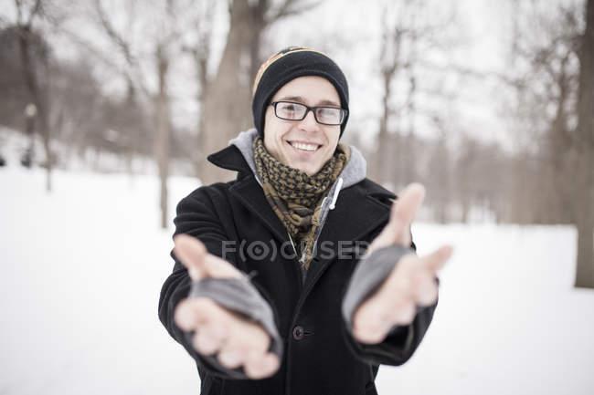 Junger Mann im Freien im Winter lächelnd und sah in der Kamera mit ausgestreckten Armen im park — Stockfoto