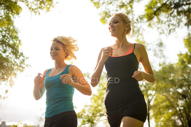 Two women jogging together in park in soft sunlight — Stock Photo