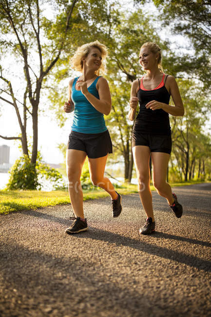 Two young women jogging together in park — Stock Photo