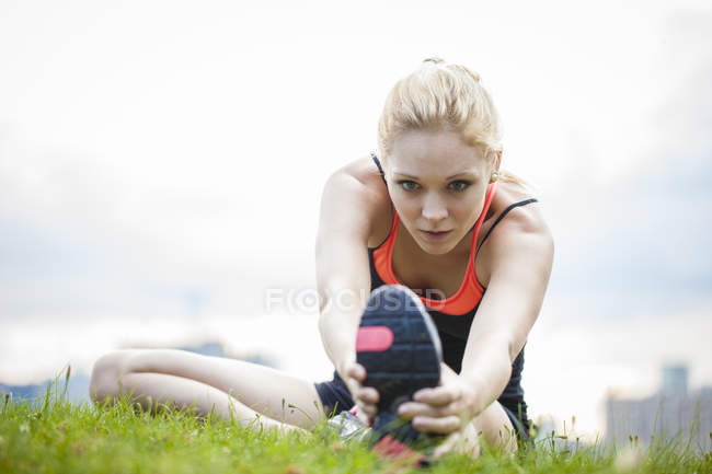 Young female athlete stretching legs in city park — Stock Photo