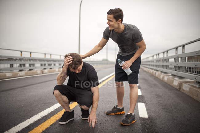 Atleta maschio solidale aiutando amico cercando di reidratare durante l'allenamento, Montreal, Quebec, Canada — Foto stock