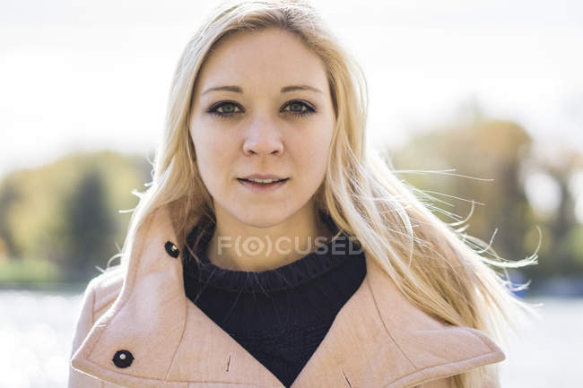 Portrait of blonde woman in autumn clothing looking in camera in park, Montreal, Quebec, Canada — Stock Photo