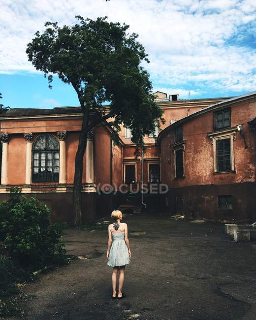 Girl looking at old house — Stock Photo