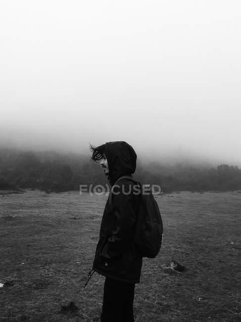 Hombre de pie en el campo de niebla - foto de stock