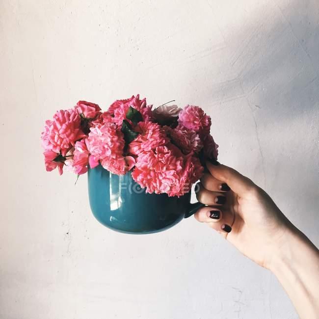 Женские руки, держащей кружку с цветами — стоковое фото