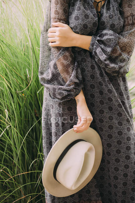 Femme debout et tenant le chapeau — Photo de stock