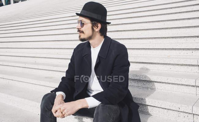 Hombre sentado en las escaleras - foto de stock