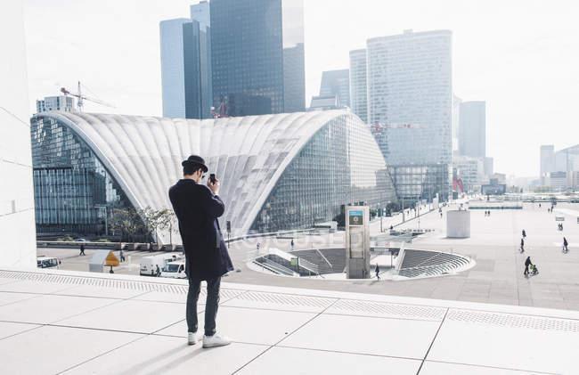 Homem tirando fotos de edifícios comerciais — Fotografia de Stock