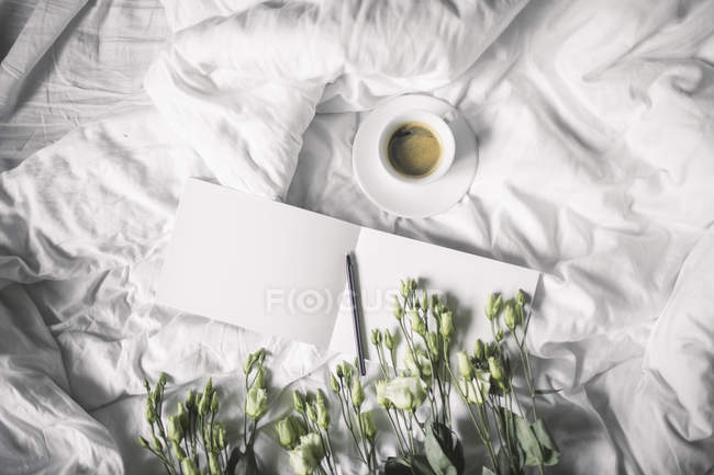 Cup of coffee on bedsheet — Stock Photo
