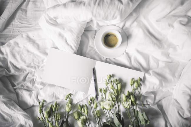 Чашка кофе на простыня — стоковое фото
