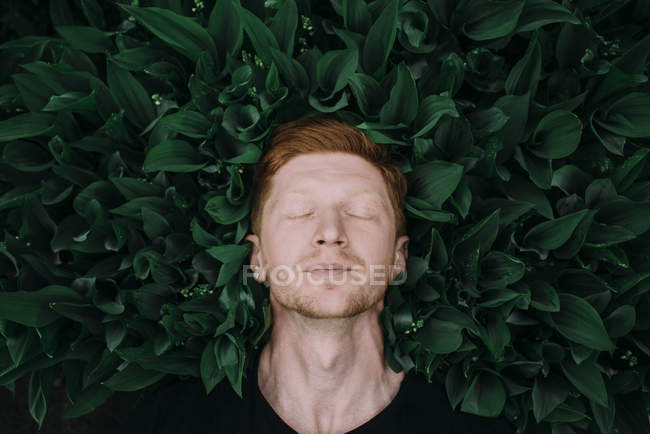Guy lying on lilies of valley — Stock Photo