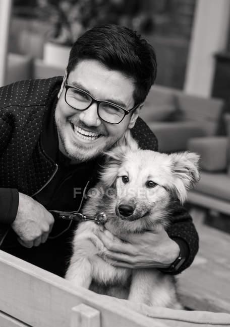 Человек с собакой, улыбающийся на камеру — стоковое фото