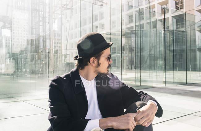 Bearded man sitting on asphalt — Stock Photo