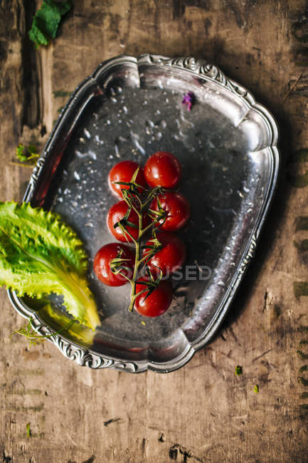 Bunch of cherry tomatoes with lettuce — Stock Photo