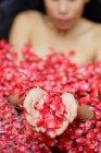 Donna nella vasca con petali di rosa — Foto stock