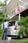Paar wäscht Auto — Stockfoto