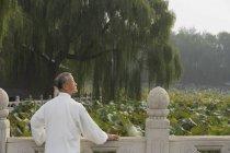 Hombre se inclina en una barandilla - foto de stock