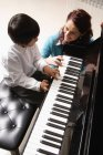 Хлопчик, навчитися грати на фортепіано з вихователем — стокове фото