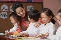 Crianças em idade escolar com o professor na classe — Fotografia de Stock