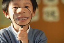 Schoolboy showing teeth in magnifying glass — Stock Photo
