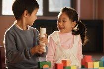 Garçon et fille jouant avec blocs de construction — Photo de stock