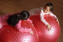 Deux filles appuyées sur des balles de fitness — Photo de stock