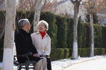 Пожилая пара сидит на скамейке в парке — стоковое фото