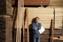 Man leaning against a stack of lumber — Stock Photo